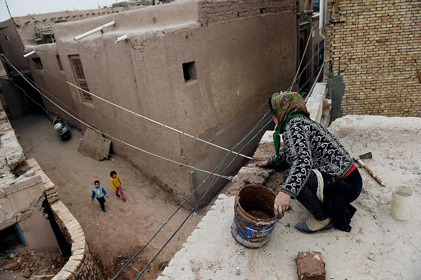 A woman repairing a roof in Kashgar in China's western Xinjiang province in April. With the increase in violence in the region, the authorities have banned veils, burqas and other Islamic forms of dress.