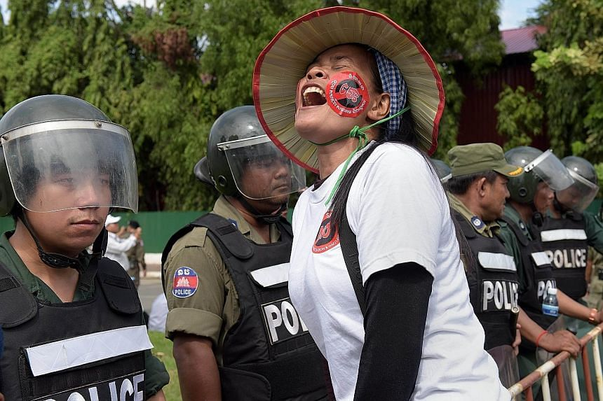A Cambodian protester shouting slogans in front of a police line near the National Assembly in Phnom Penh on Monday. More than 700 people protested outside the National Assembly as members of the ruling party passed the law.