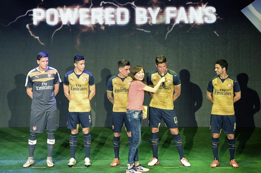 Event host Jade Seah interviewing Arsenal striker Olivier Giroud - along with his Gunners team-mates (from left) Wojciech Szczesny, Gabriel Paulista, Hector Bellerin and Mikel Arteta - at the launch of the club's new away kit at the Esplanade Outdoor