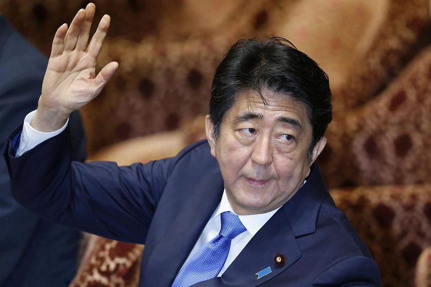 Japan's Prime Minister Shinzo Abe raises his hands during the lower house special committee session on the security-related legislation at the parliament in Tokyo on July 15, 2015.