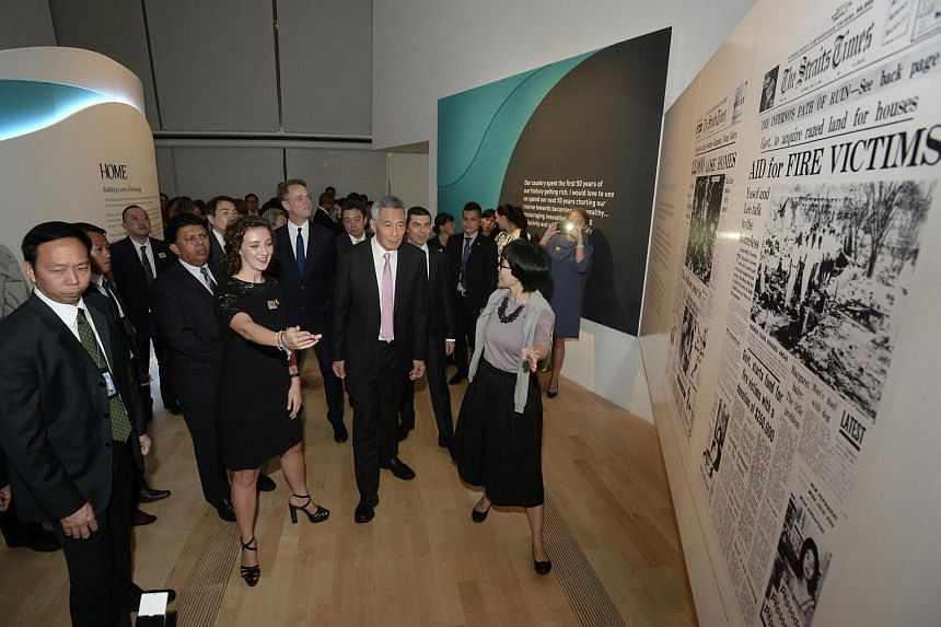 Prime Minister Lee Hsien Loong looking at blow-ups of past articles from The Straits Times, at the newspaper's ST170 exhibition grand opening at the ArtScience Museum on July 15, 2015.