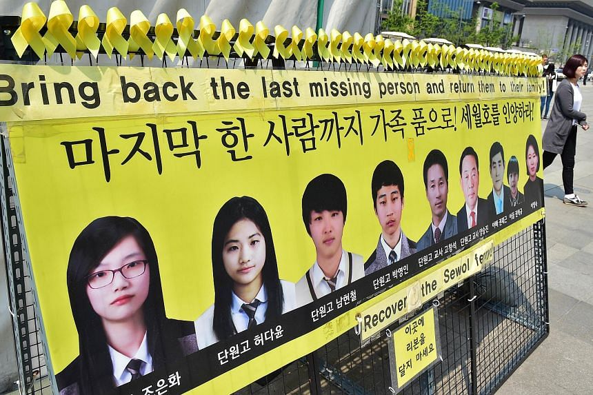A woman walks past portraits of missing people from South Korea's Sewol ferry disaster at the Gwanghwamun square.