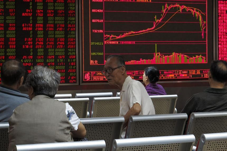 Stock investors keep watch as an electronic screen shows market movement information at a securities brokerage house in Beijing, China, 14 July 2015. PHOTO: EPA