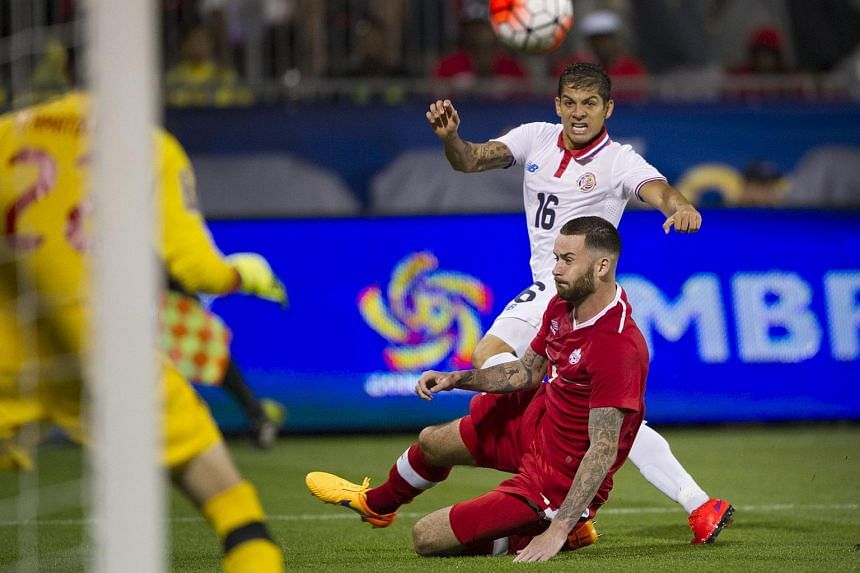 Christian Gamboa of Costa Rica (in white) sends the ball wide of the net as defender David Edgar of Canada keeps a close eye during the second half of their Concacaf Gold Cup match in Toronto.