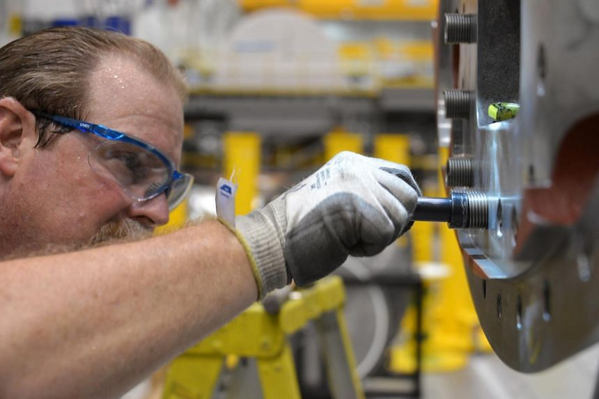 A file picture of a technician tapping a thread into an exhaust casing at the Mitsubishi-Hitachi Power Systems America plant in Pooler, Georgia, U.S., on July 9, 2015. Factory output in the U.S. was little changed in June for a second month, held bac