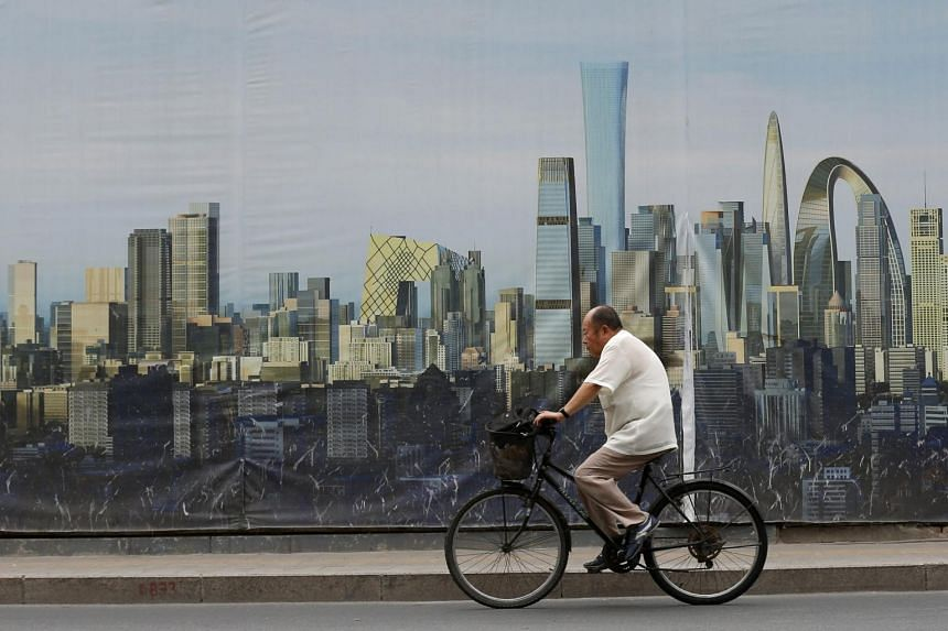 A cyclist passes a poster showing a future design near a construction site in Beijing, China on 15 July 2015. China's economy grew in the second quarter of this year by 7 per cent year-on-year, the National Bureau of Statistics announced in Beijing,