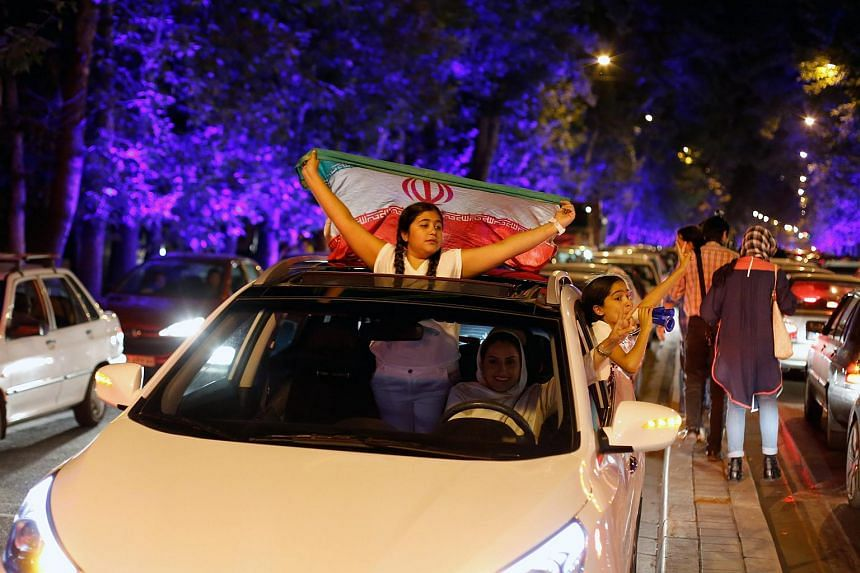 An Iranian girl holds Iran's national flag as people celebrate in the street of Tehran, Iran, on July 14, after nuclear talks between Iran and World powers ended in Vienna, Austria. The successful outcome of the Iran nuclear talks shows China's mantr