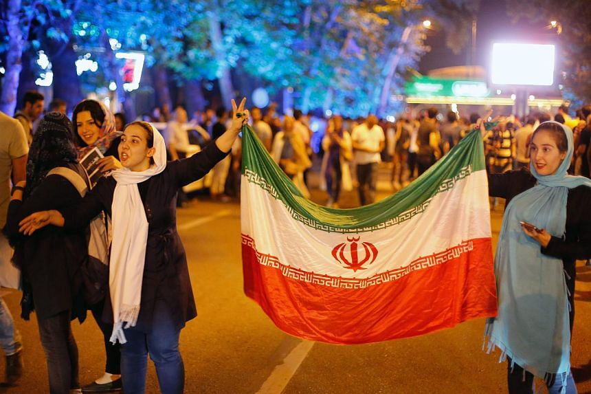 Iranians holding national flags as they celebrate their country's nuclear deal in the streets of Tehran.