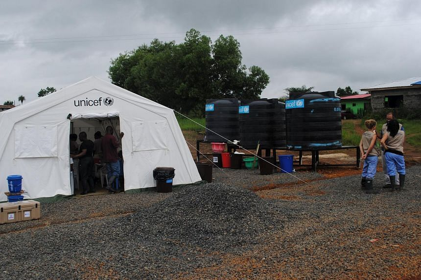Health workers gather at a clinic in Nedowein, Liberia on July 10, 2015.