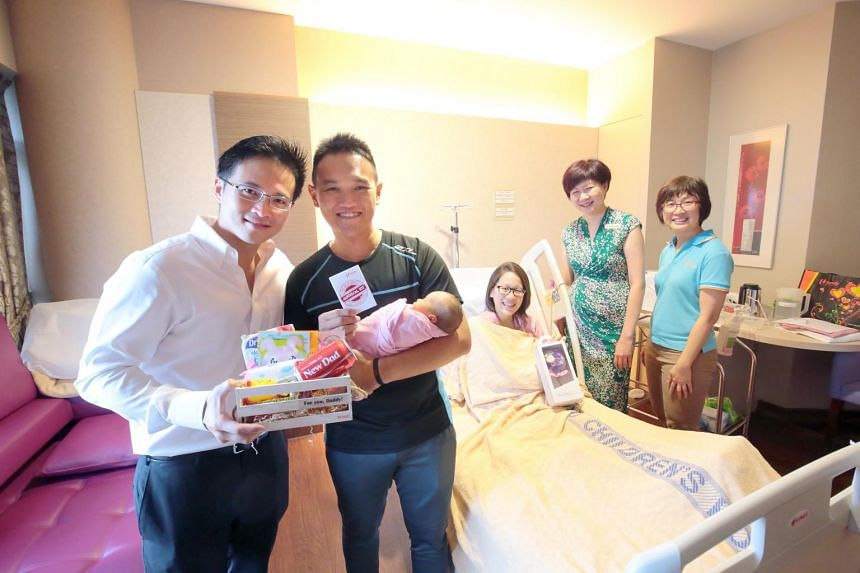 NTUC Youth Development Unit Director and soon-to-be father, Mr Desmond Choo distributing New Dad's Survival Kits to new fathers in KKH.