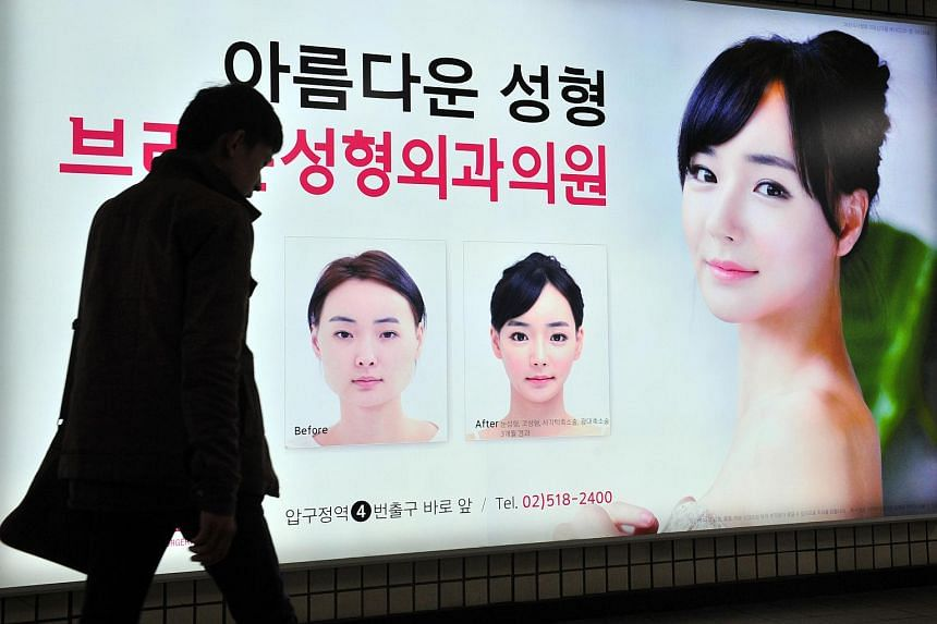 A pedestrian walks past an advertisement for plastic surgery clinic at a subway station in Seoul on March 26, 2014.