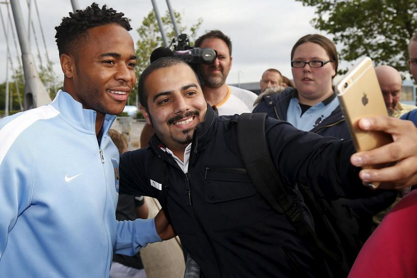 New Manchester City signing Raheem Sterling poses for photographs with supporters as he leaves the club's Etihad Stadium.