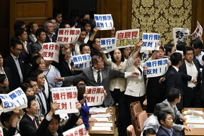 Opposition lawmakers hold banners reading 'Against forcible passage!' at the end of a committee session on controversial security bills at the parliament in Tokyo, Japan, 15 July 2015.