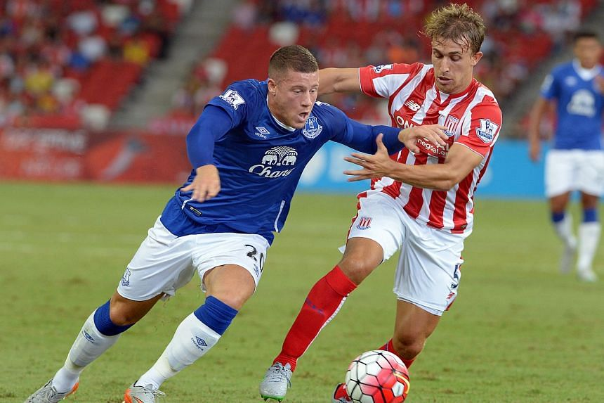 Everton's Ross Barkley (in blue) and Stoke's Marc Muniesa tussle for the ball during their match at the National Stadium in Singapore on July 15, 2015.