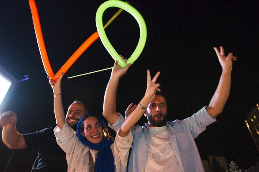 Iranians celebrating in the streets of Tehran following a nuclear deal with major powers.