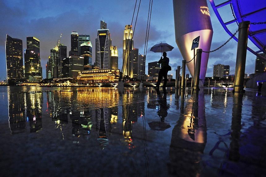The Singapore skyline is seen reflected in a puddle of water at the Esplanade's outdoor theatre.