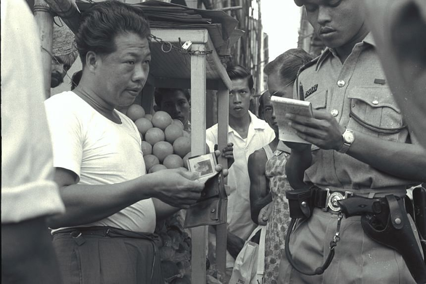 Police out to take action against suspected illegal hawkers in Raffles Place in 1959.