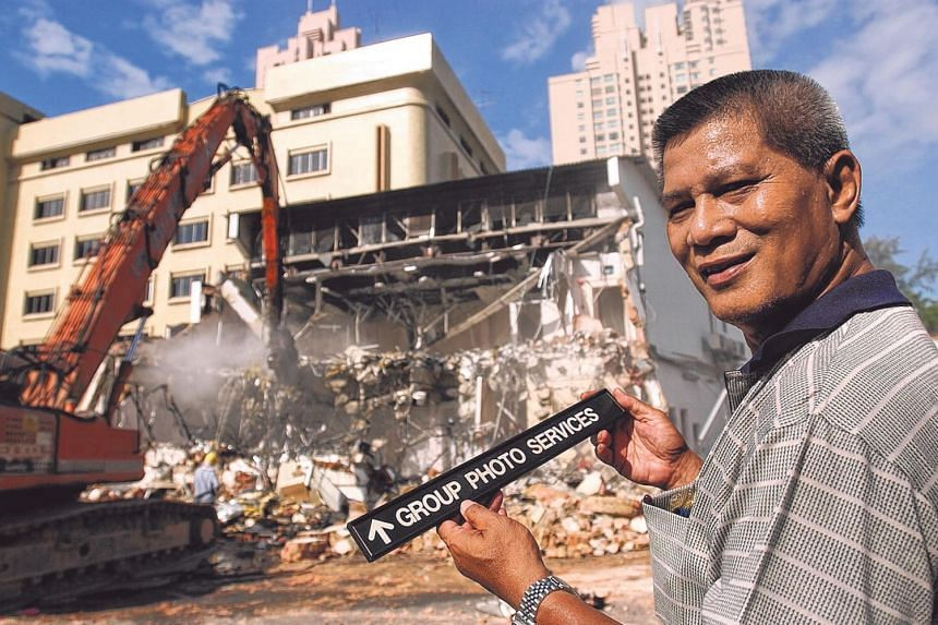 Demolition of the Times House building begins in 2004 to make way for redevelopment, as ex-ST TV cameraman Shahriya Yahaya holds the name plate of the department where he used to work.