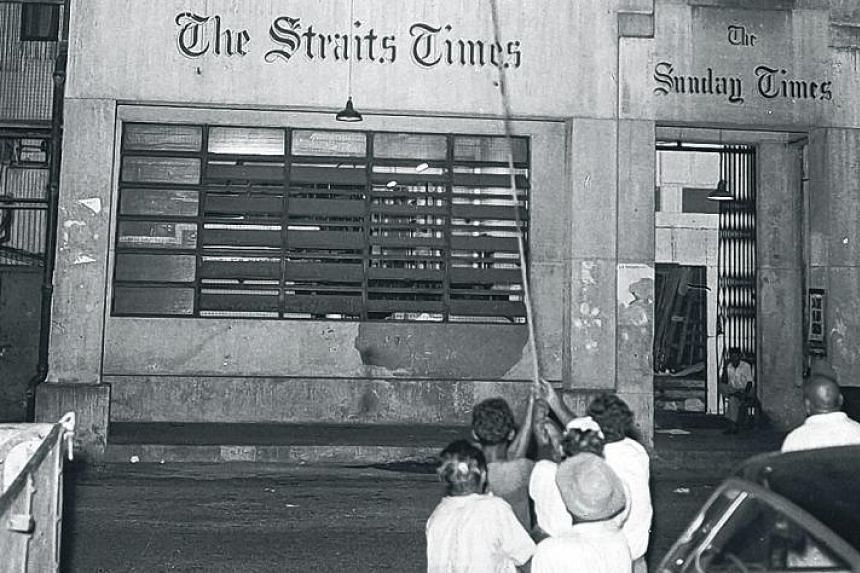 A linotype machine weighing three-quarters of a tonne being lowered from the second floor of the Straits Times office in Cecil Street before it is moved to the new building in River Valley.