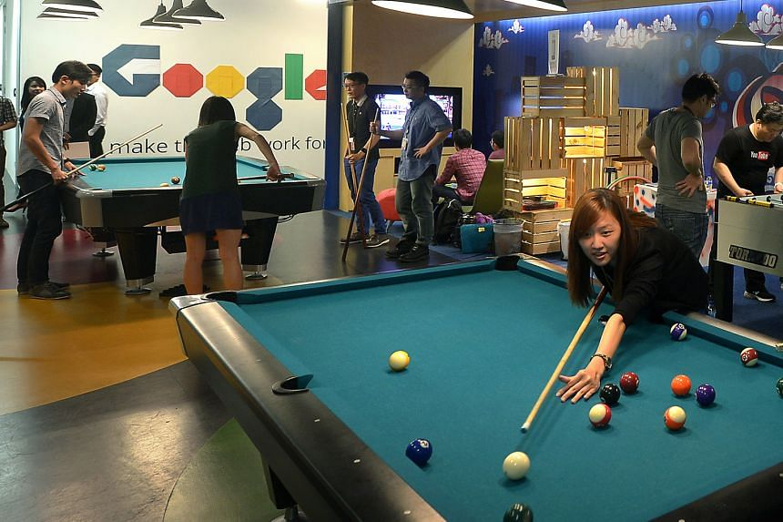 Google employees chill out at one of the many recreational spaces at Google Singapore's office. The space includes foosball tables, pool tables and console gaming lounges. Other perks include a free breakfast and lunch buffet as well as dedicated nap
