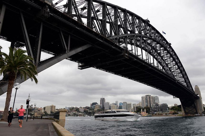 A boat crosses under the Sydney Harbour Bridge in Sydney, Australia. As Australia's mining-investment boom winds down, the central bank has been relying on a steady flow of new migrants to boost the economy.