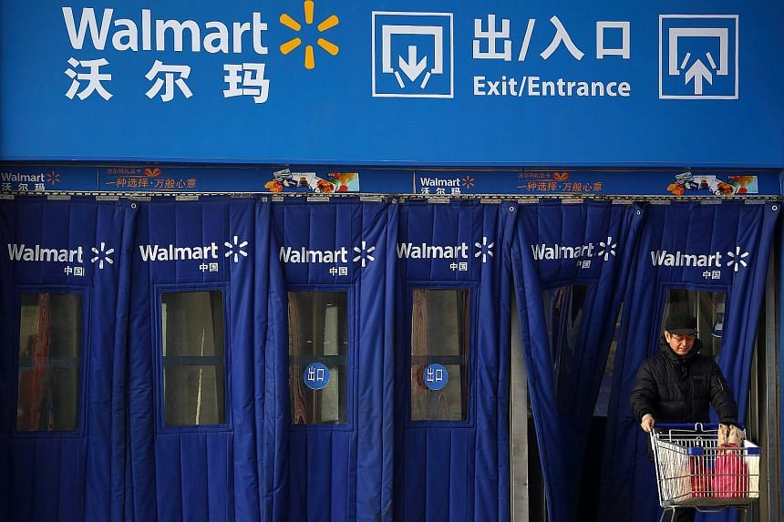 A customer pushing a shopping cart exits a Wal-Mart Stores Inc. supercentre store in Beijing, China.