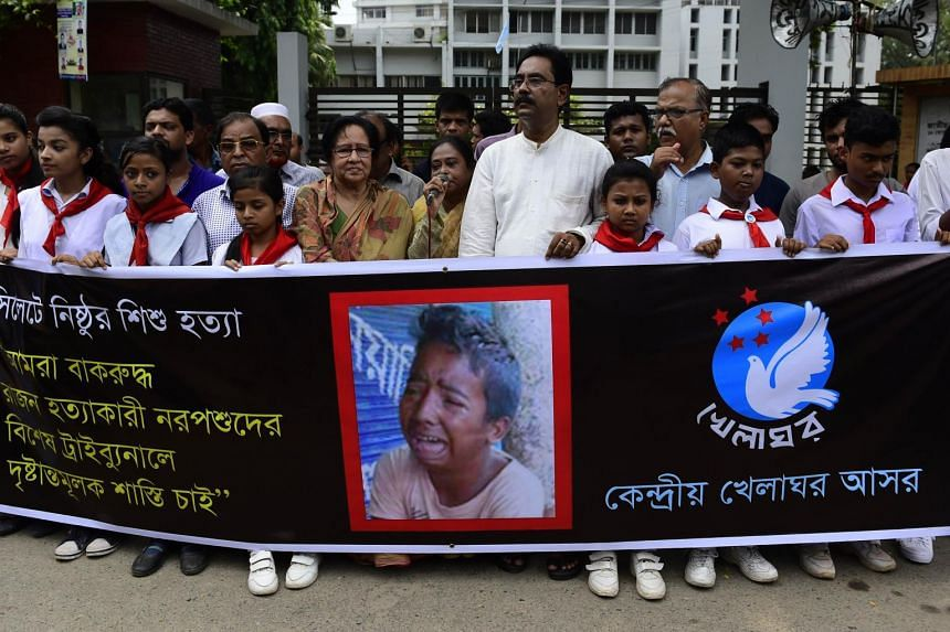 Bangladeshi protesters carry a banner during a demonstration against the lynching of 13-year-old Samiul Alam Rajon, in Dhaka on July 14, 2015.