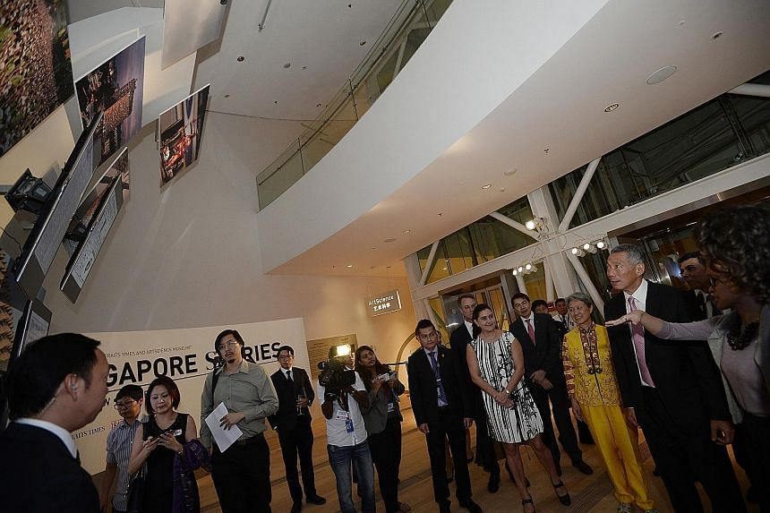 [ ]Prime Minister Lee Hsien Loong and his wife Ho Ching at yesterday's launch of the ST170 exhibition, Singapore STories: Then. Now. Tomorrow, which depicts Singapore's history through the pages of The Straits Times.
