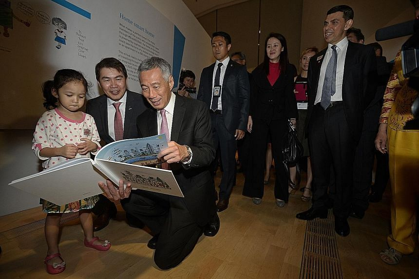 PM Lee taking a wefie with (from left) SPH English, Malay, Tamil Media Group editor-in-chief Patrick Daniel, ST editor Warren Fernandez, Marina Bay Sands chief George Tanasijevich and Mr Lee's wife Ho Ching. A drawing of Mr Lee taking a selfie agains