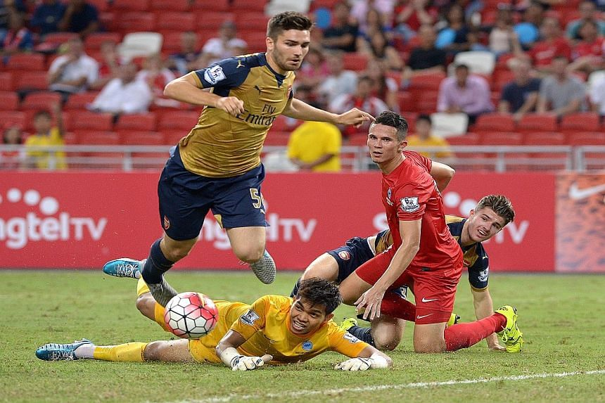 Arsenal's Jon Toral (left) tripping over Singapore Selection goalkeeper Izwan Mahbud, resulting in a penalty.