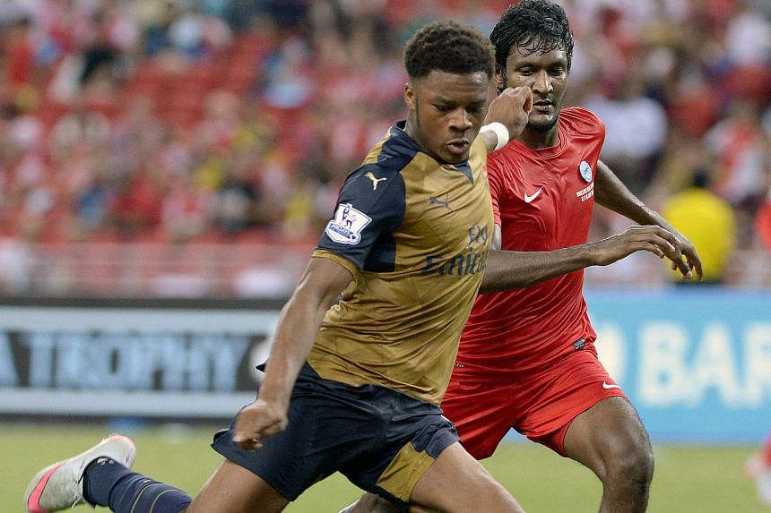 Arsenal's Chuba Akpom (left), watched by Singapore's Madhu Mohana, taking a shot at goal.