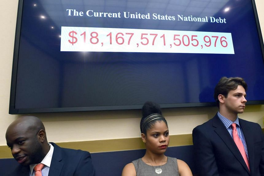 Capitol Hill staffers stand near a TV monitor showing the quickly changing national debt.