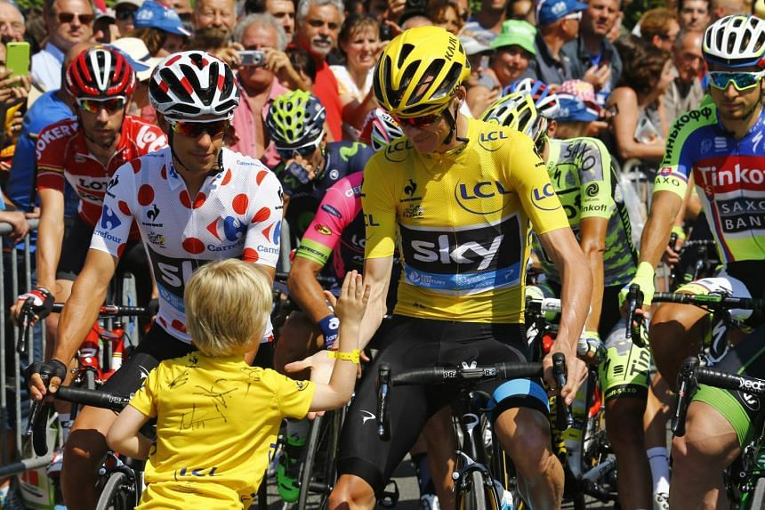 Froome shakes hands with a child before the start of the 188km 11th stage of the Tour de France.
