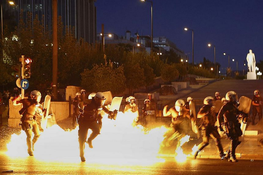 Riot policemen trying to avoid an exploding petrol bomb during clashes in Athens.