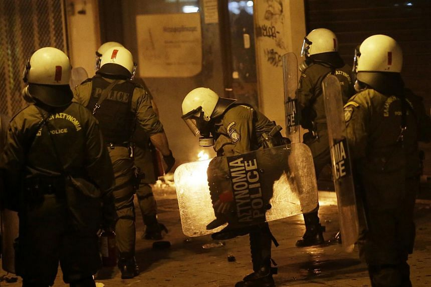 A police officer adjusting his gear during clashes with protesters on Syntagma Square in central Athens.