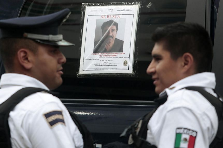 """Two Federal Police officers stand next to a patrol car with a picture of fugitive drug lord Joaquin """"El Chapo"""" Guzman on its window, in Acapulco, Guerrero State, Mexico, on July 14, 2015."""