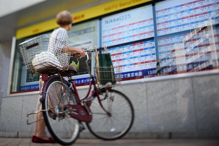 A woman holding a bicycle looks at an electronic stock board outside a security firm in Japan.