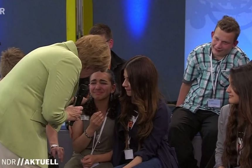 A screenshot from the footage of Angela Merkel comforting the Palestinian girl.