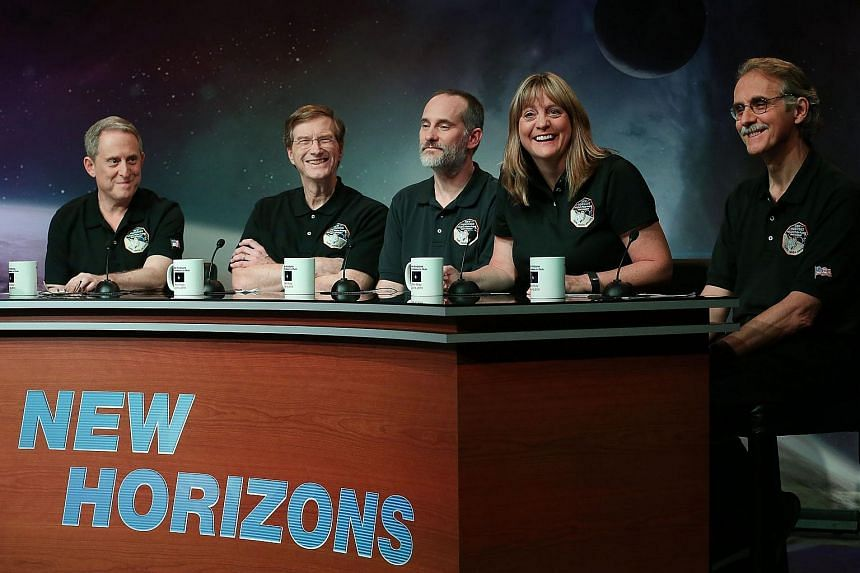 (From left) Principal investigator Alan Stern, project scientist Hal Weaver, investigator Will Grundy, project scientist Cathy Olkin and imaging team leader John Spencer celebrate after seeing images from the New Horizons spacecraft.