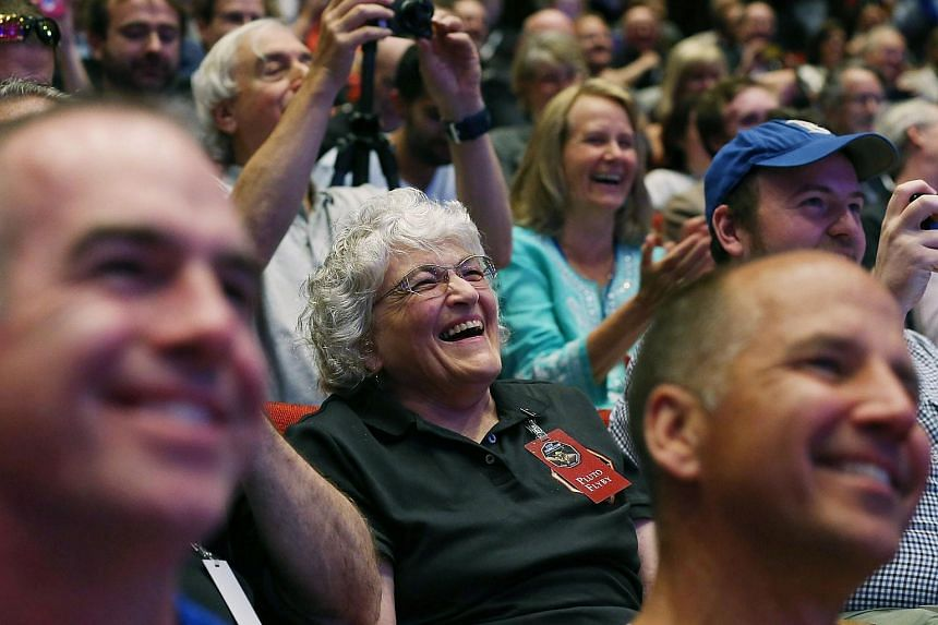 Annette Tombaugh Sitze (centre), daughter of Pluto discoverer Clyde Tombaugh, watches as images of Pluto that were taken by the New Horizons spacecraft.