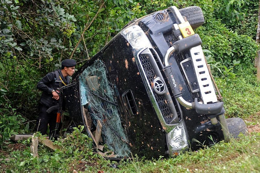 A Thai ranger inspects a pick-up truck that was ambushed by suspected separatist militants in the Rangae district of Thailand's Narathiwat province on July 14, 2015.