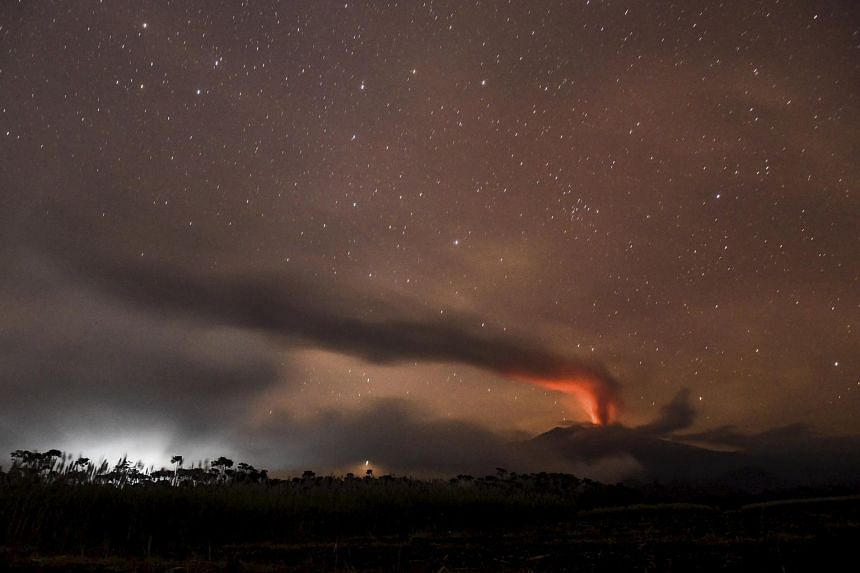 Volcanic ash and clouds are illuminated by lava from the crater of Mount Raung, as seen from Songgon, Banyuwangi East Java, Indonesia on July 11, 2015.