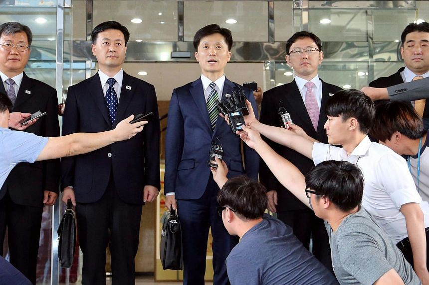 Mr Lee Sang-Min (centre), a senior South Korean Unification Ministry official, speaks to the media in Seoul on July 16, 2015, before leaving for North Korea to hold talks on a wage dispute at their joint industrial zone.