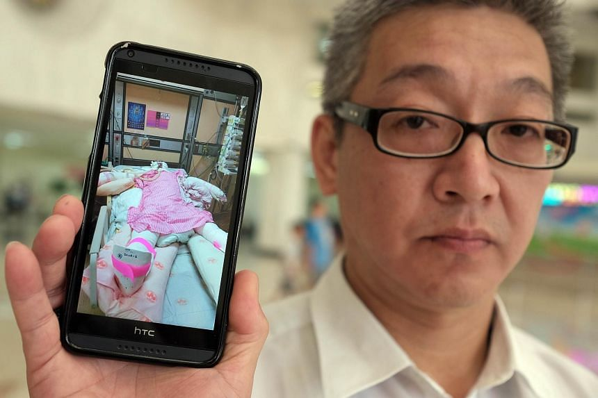 Michael Chu, father of 18-year-old burn victim Julie, displaying a photo of her at a hospital in Taipei.