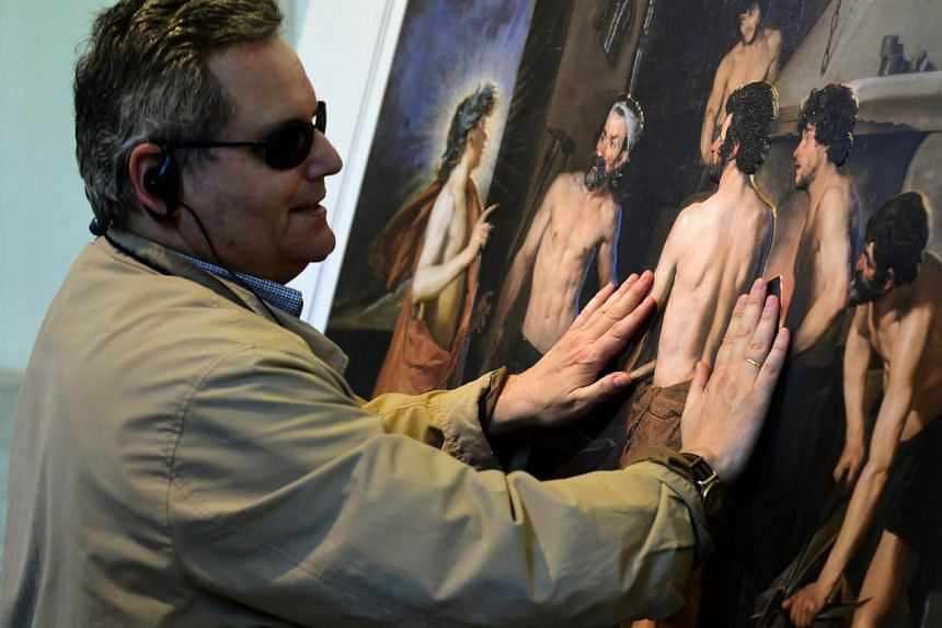 """Jose Pedro Gonzalez, a 56-year-old blind visitor touches a painting using a relief painting technique that adds volume and texture, a copy of 15th century master Diego de Velazquez's most famous paintings, """"Apollo in the Forge of Vulcan"""", part of exh"""