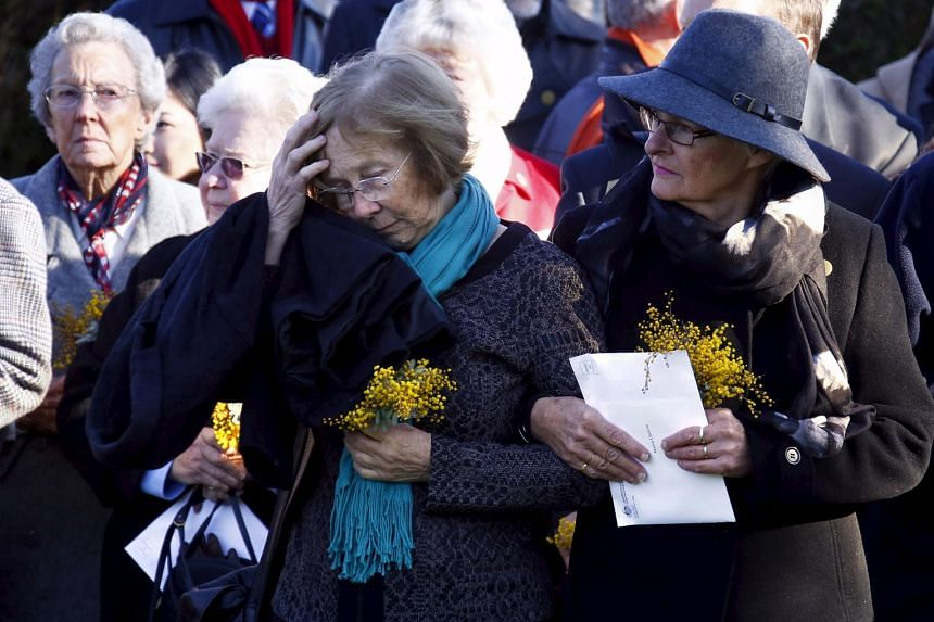 Relatives of the Australian victims of Malaysia Airlines jet MH17 react during a service for the unveiling of a memorial outside Parliament House in Canberra, Australia, on July 17, 2015.