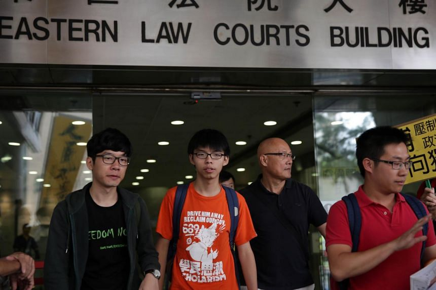 Pro-democracy activists Nathan Law, Joshua Wong, Albert Chan and Raphael Wong leave after their appearance at the Eastern Law Courts in Hong Kong on July 17, 2015.