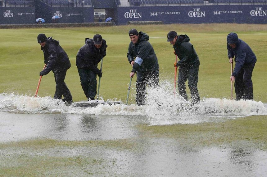 Groundstaff remove water from the first hole after torrential rain forced play to be suspended during the second round of the British Open golf championship on the Old Course in St. Andrews, Scotland, on July 17, 2015.