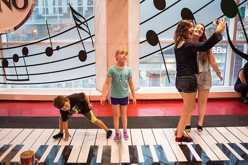 Children playing on the Big Piano, made famous by the 1988 Tom Hanks' movie Big, in FAO Schwarz toy store in New York.