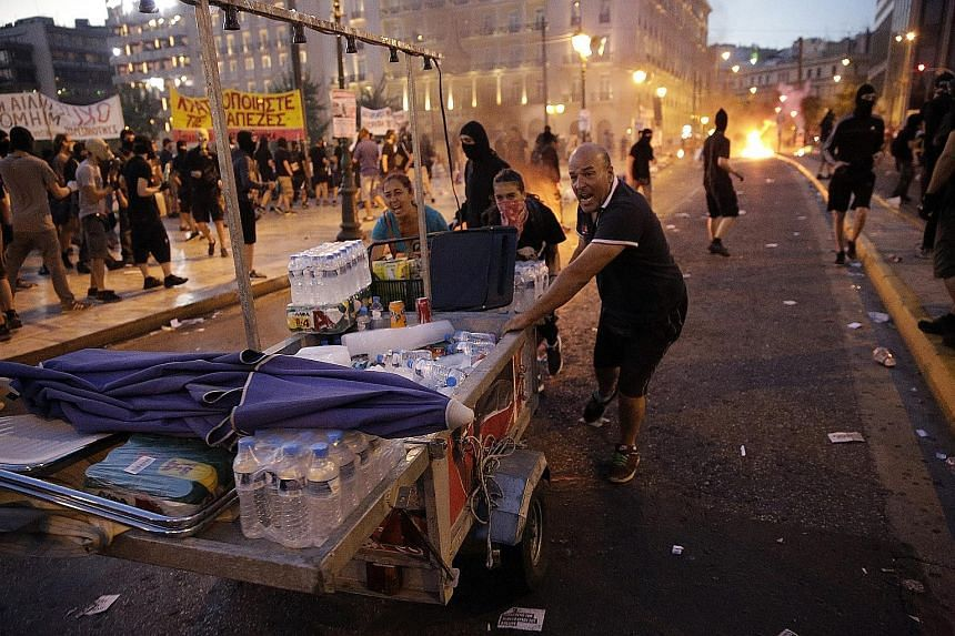 Food vendors fleeing Syntagma Square in Athens on Wednesday during police clashes with protesters angry at the austerity measures that were passed by the Greek Parliament in return for talks on a new aid package from the euro zone.